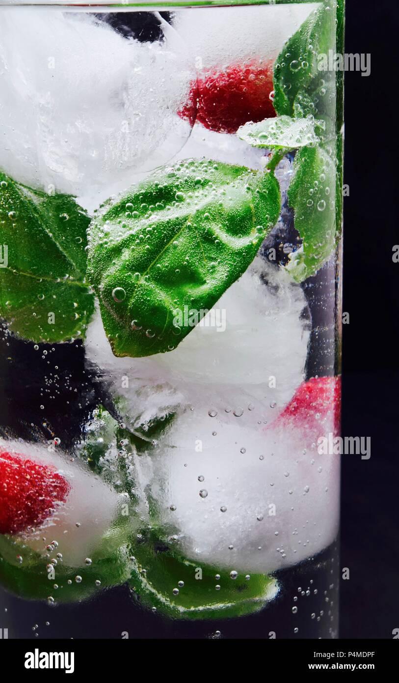 Cubitos de hielo con frambuesas y hojas de albahaca en un vaso de agua. Imagen De Stock