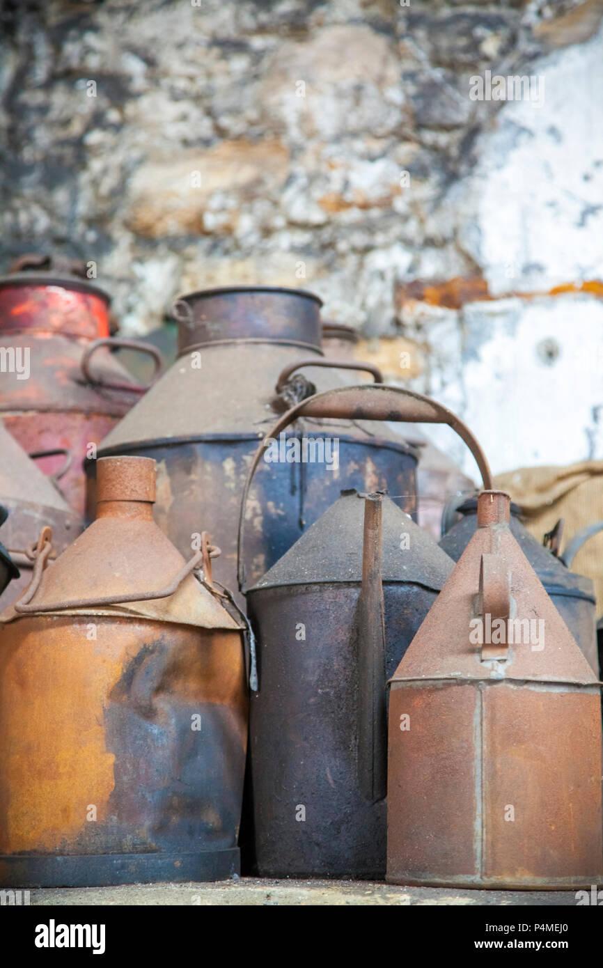 Un grupo de latas oxidadas en un antiguo taller Foto de stock