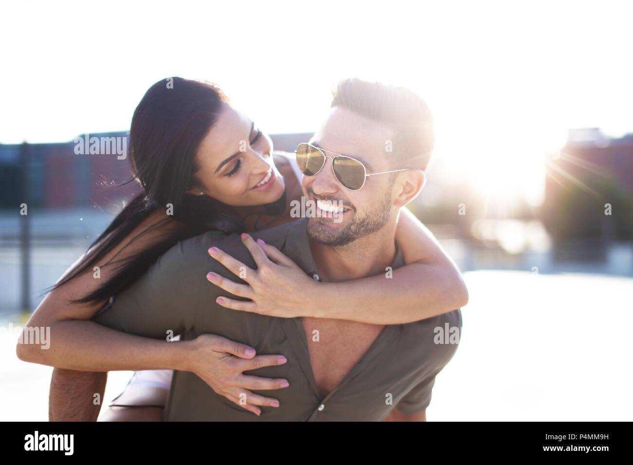 Feliz joven abrazando el hombre elegante desde afuera en el sol Imagen De Stock