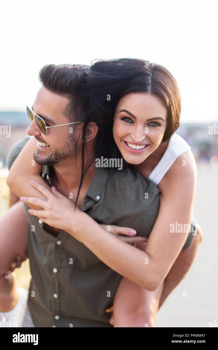 Novia elegante hombre llevando en la espalda al aire libre, pareja en alegría y diversión Imagen De Stock