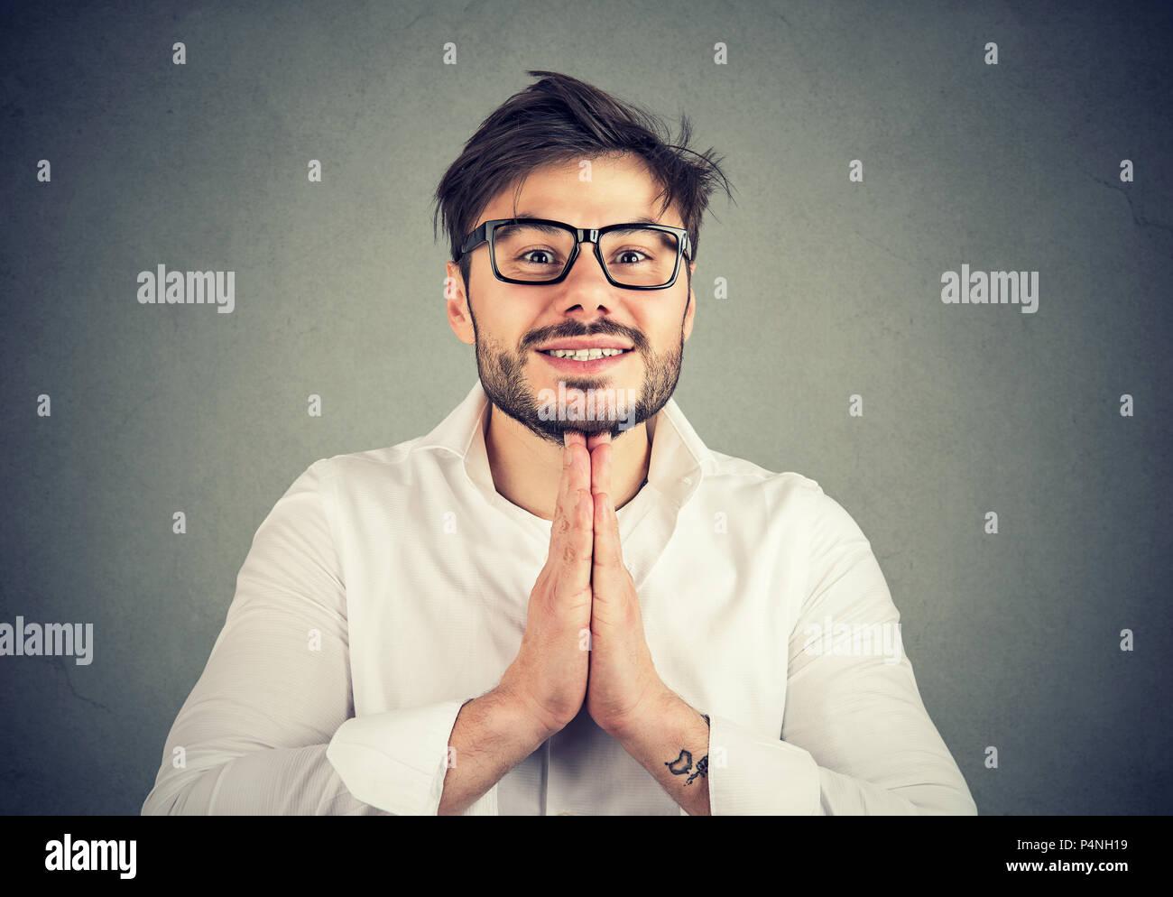 Chico joven con barba y gafas en las manos de la camisa junto a la mendicidad y gestos pidiendo su gracia sobre fondo gris Imagen De Stock