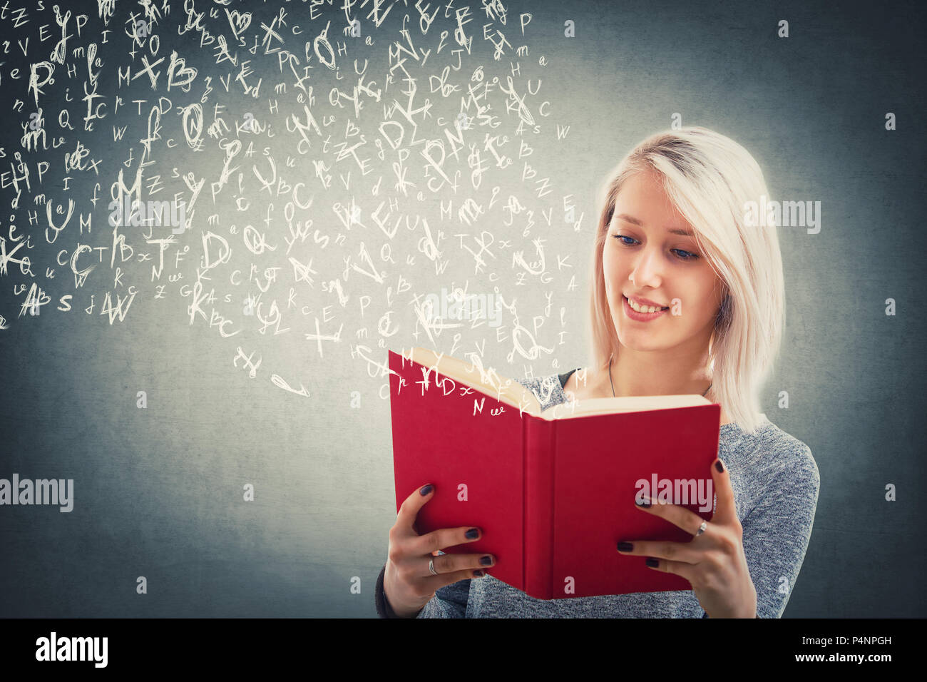 Hermosa chica rubia leer y volar las letras del alfabeto escapar de el libro rojo. La magia de la charla. Profesor de la escuela de jóvenes estudiando, educativa y Foto de stock
