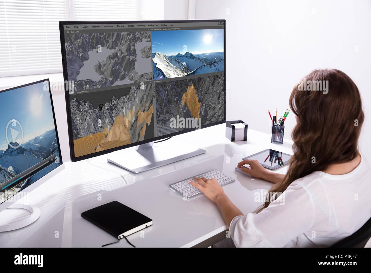 Vista trasera de una mujer trabajando en paisaje 3D en el equipo de Office Imagen De Stock