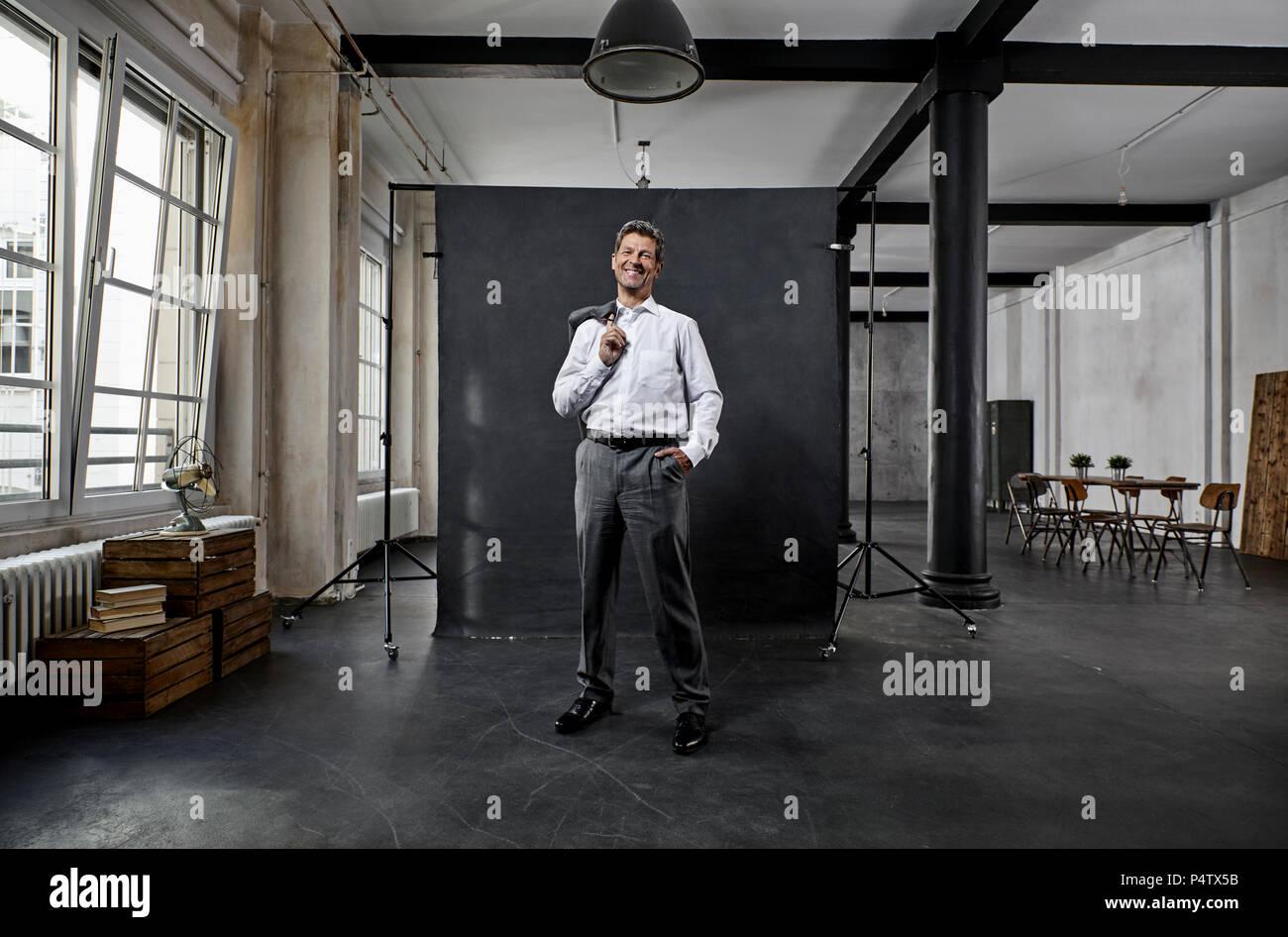 Retrato del hombre de negocios maduros delante del telón de fondo negro en loft Imagen De Stock
