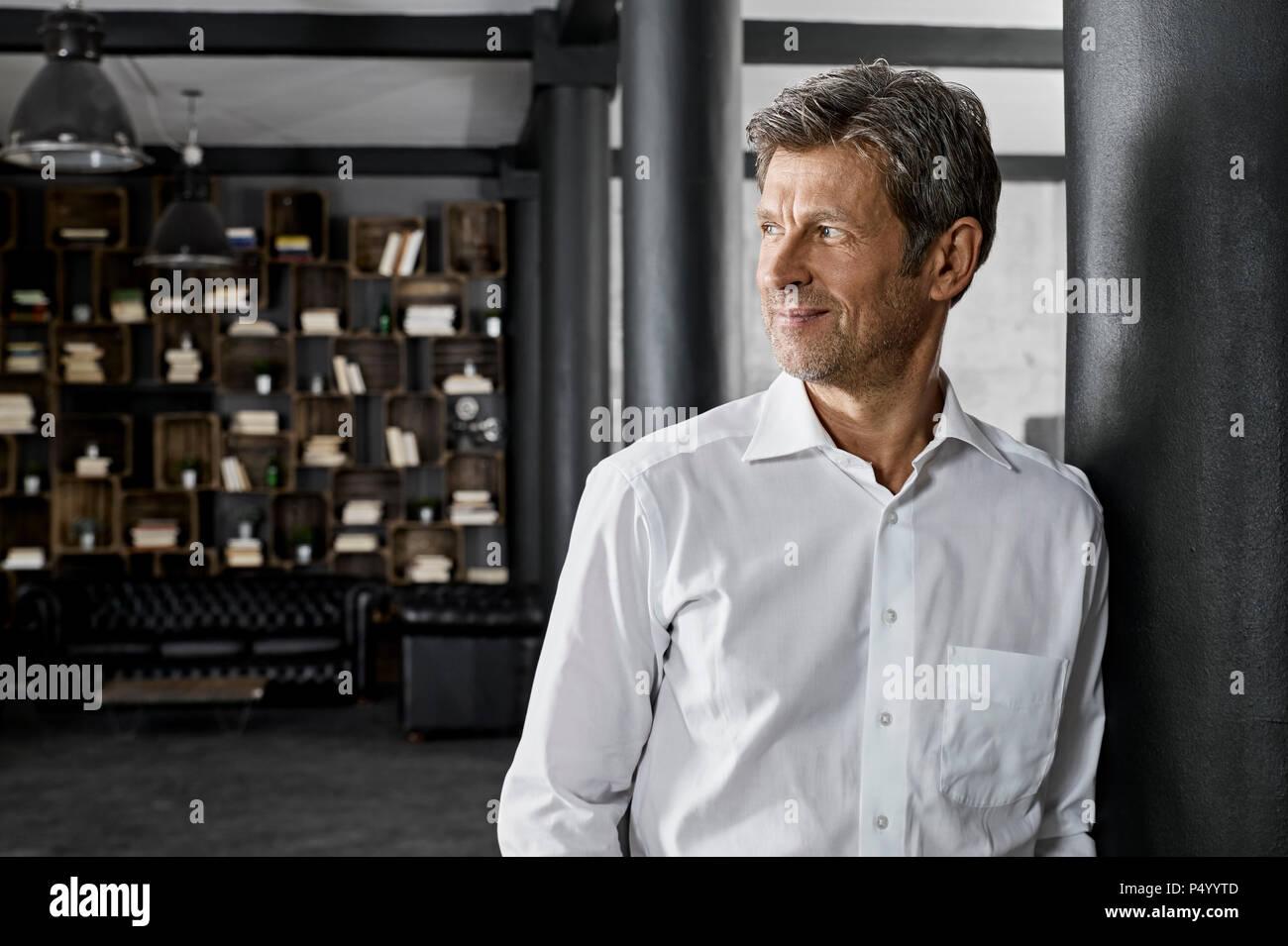 Hombre maduro en loft apoyado contra una columna Imagen De Stock