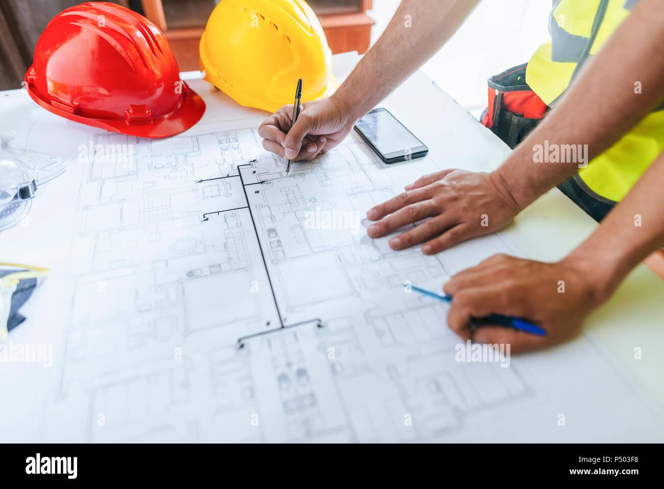 Close-up de manos de trabajadores, trabajando sobre el plano de construcción Imagen De Stock