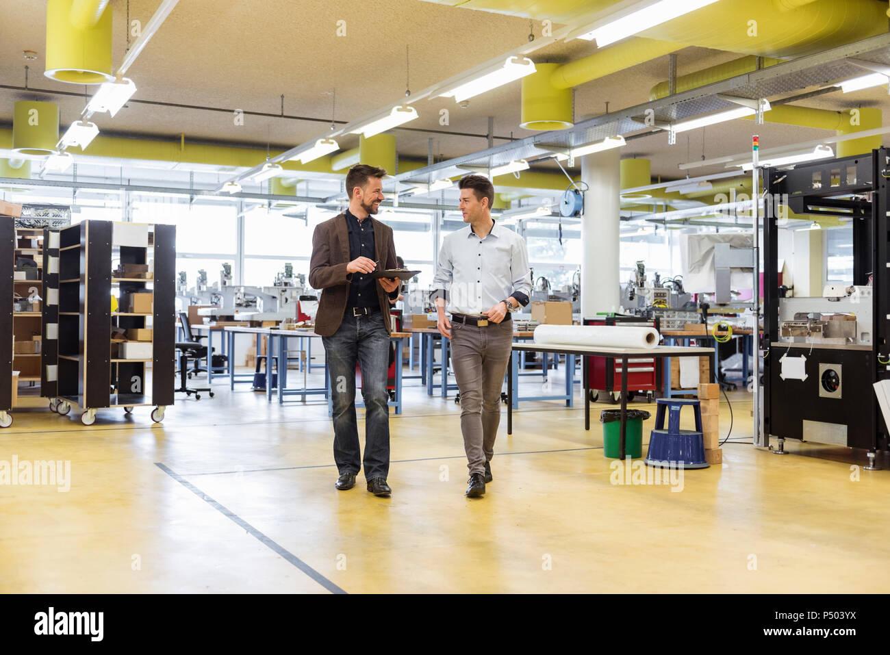 Dos hombres caminando y conversando en la fábrica. Foto de stock