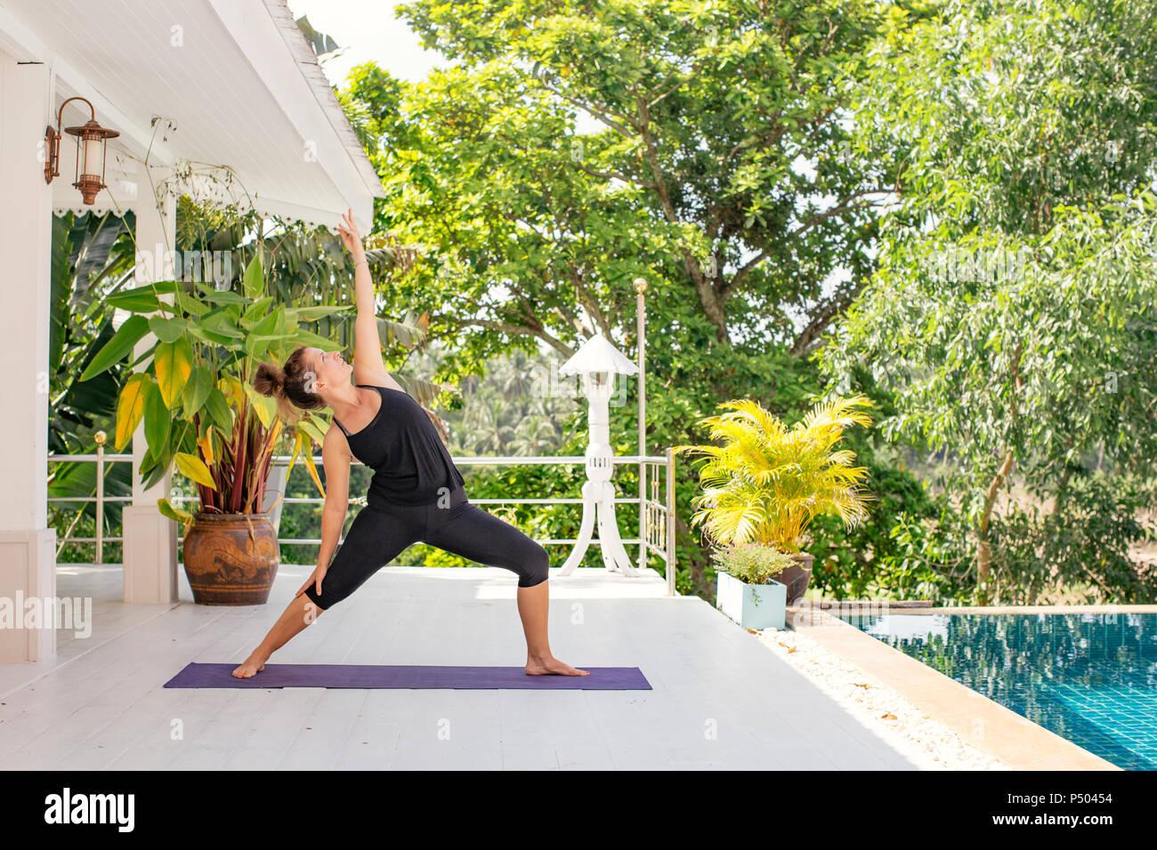Mujer Practicando Yoga En La Terraza Junto A La Piscina Foto