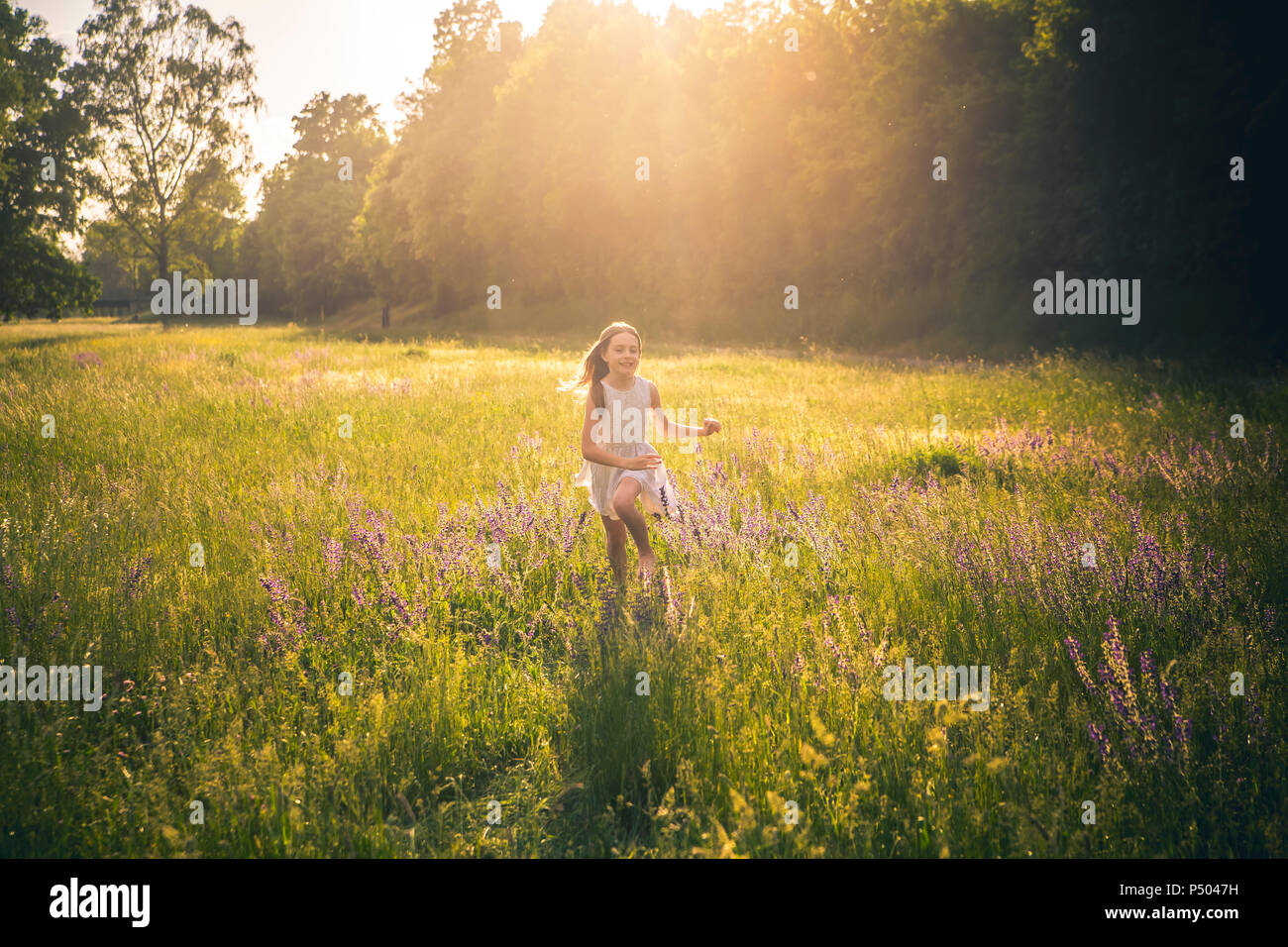 Sonriente niña corriendo en la pradera de flores en el crepúsculo de la noche Imagen De Stock