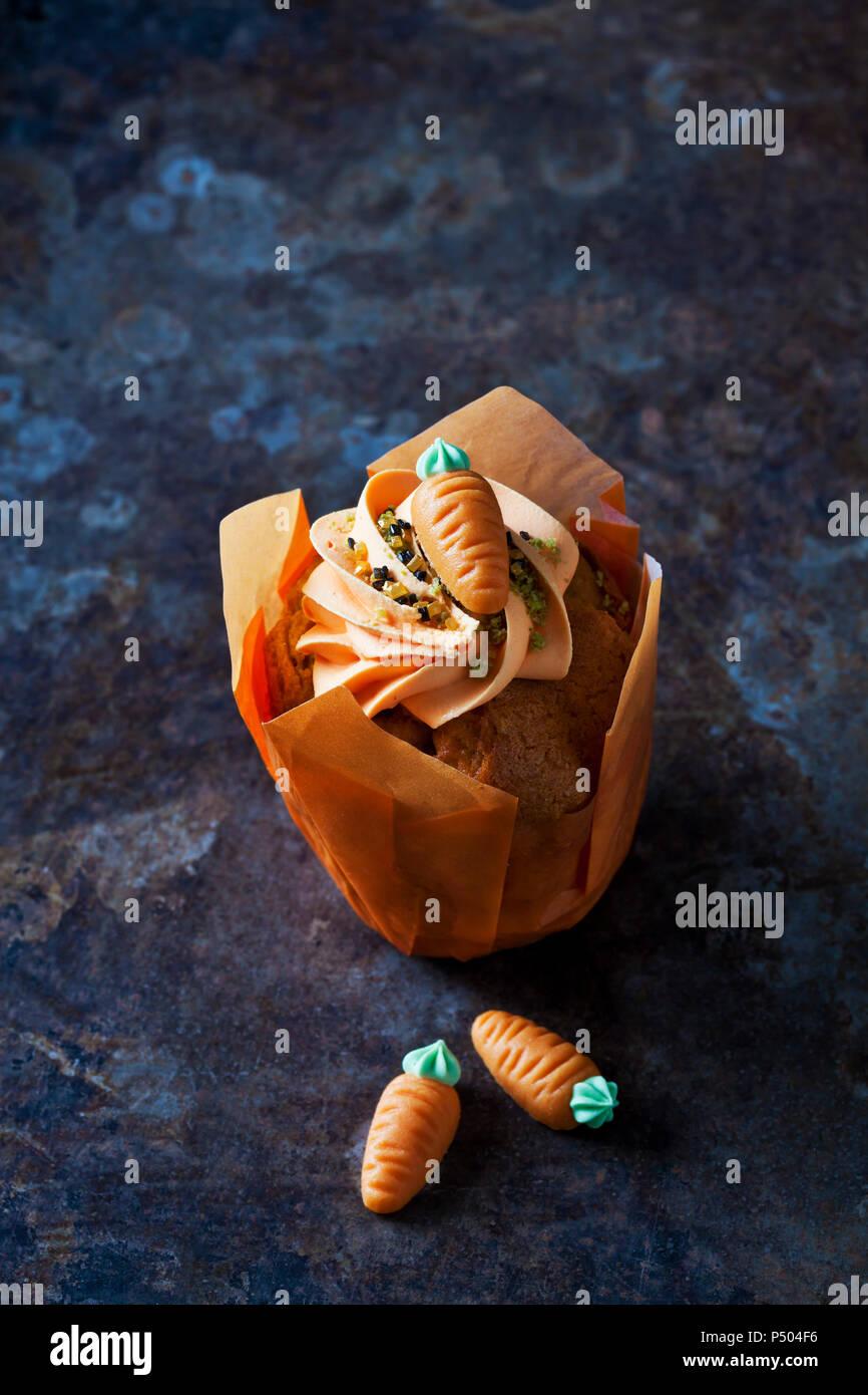 Taza de zanahoria pastel aderezado con crema topping, gránulos de azúcar y el mazapán zanahoria Imagen De Stock