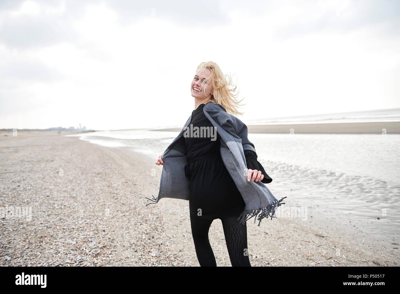 Países Bajos, retrato de mujer joven rubia corriendo en la playa Imagen De Stock