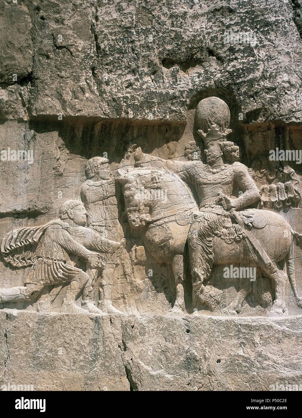 Irán. Naqsh-e Rustam. Necrópolis. Periodo sasánida. El triunfo de Sapor I (241-272) (a caballo). Sapor la victoria sobre los emperadores romanos Valeriano (rodillas) y Filipo el Árabe. Foto de stock