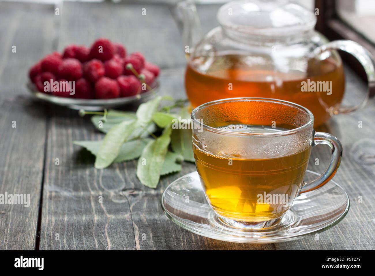 Frambuesa y té verde de un tilo en una mesa de madera Foto de stock