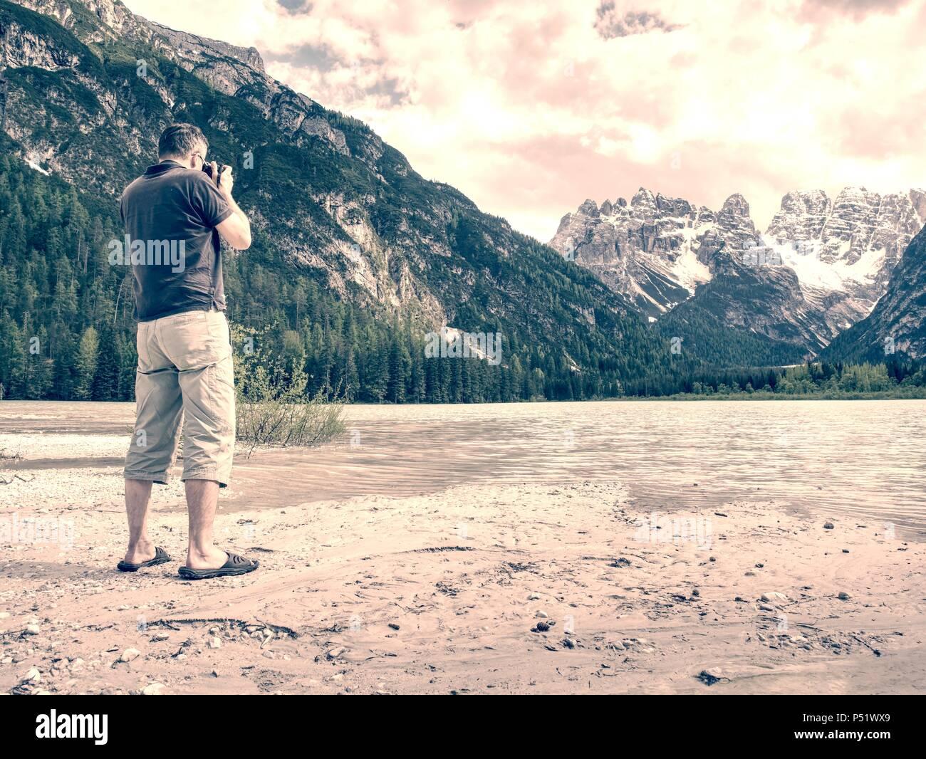 Photo Traveler está tomando fotos de la memoria de el escenario del lago. Blue Lake entre altas montañas, picos toque en azul cielo. Concepto de estilo de vida de viaje Imagen De Stock