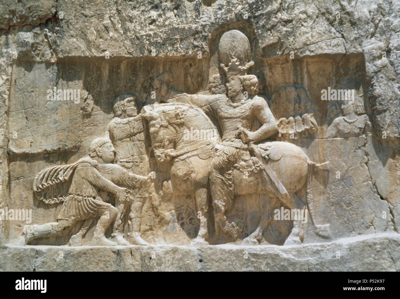 """ARTE PERSA-PERIODO SASANIDA. Bajorrelieve del """"TRIUNFO DE SEPUR I', donde se narra la rendición de los emperadores Valeriano y FILIPO 'el Arabe' tras las campañas de 252-261. A caballo el rey sasánida y arrodillado ante él, Valeriano, su prisionero hasta su muerte. Aliviar del s. III d. C. NAQSH-E ROSTAM (Naqsh-e Rustam). Provincia de Fars. República Islámica de Irán. Foto de stock"""