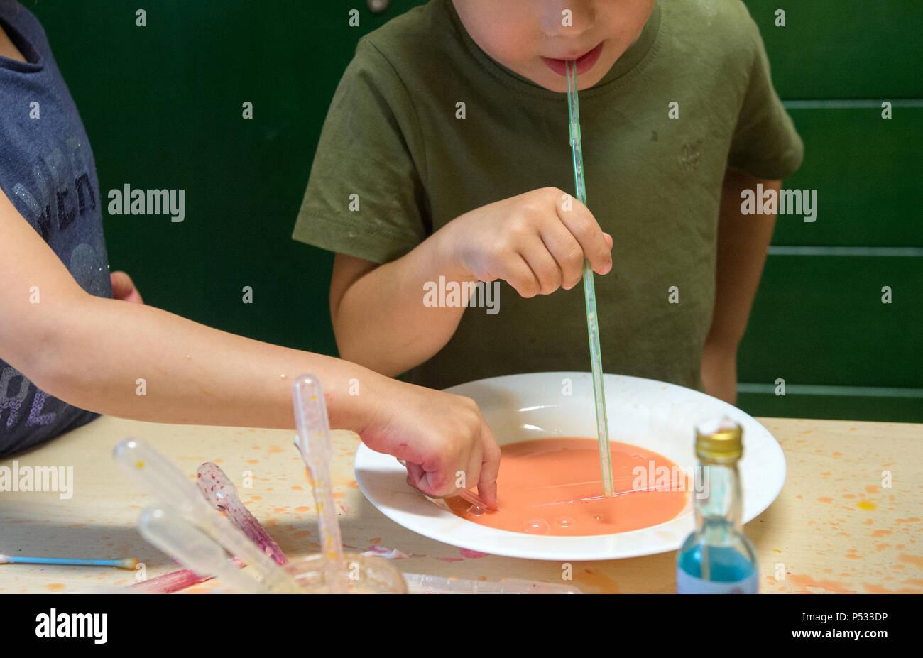 Niños jugando con líquido de colores en una guardería de niños Imagen De Stock