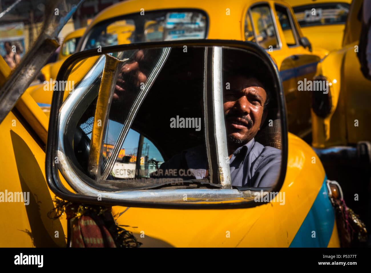 Taxi Driver como se ve desde el espejo lateral de su Hindustan Ambassador, Kolkata, India. Imagen De Stock