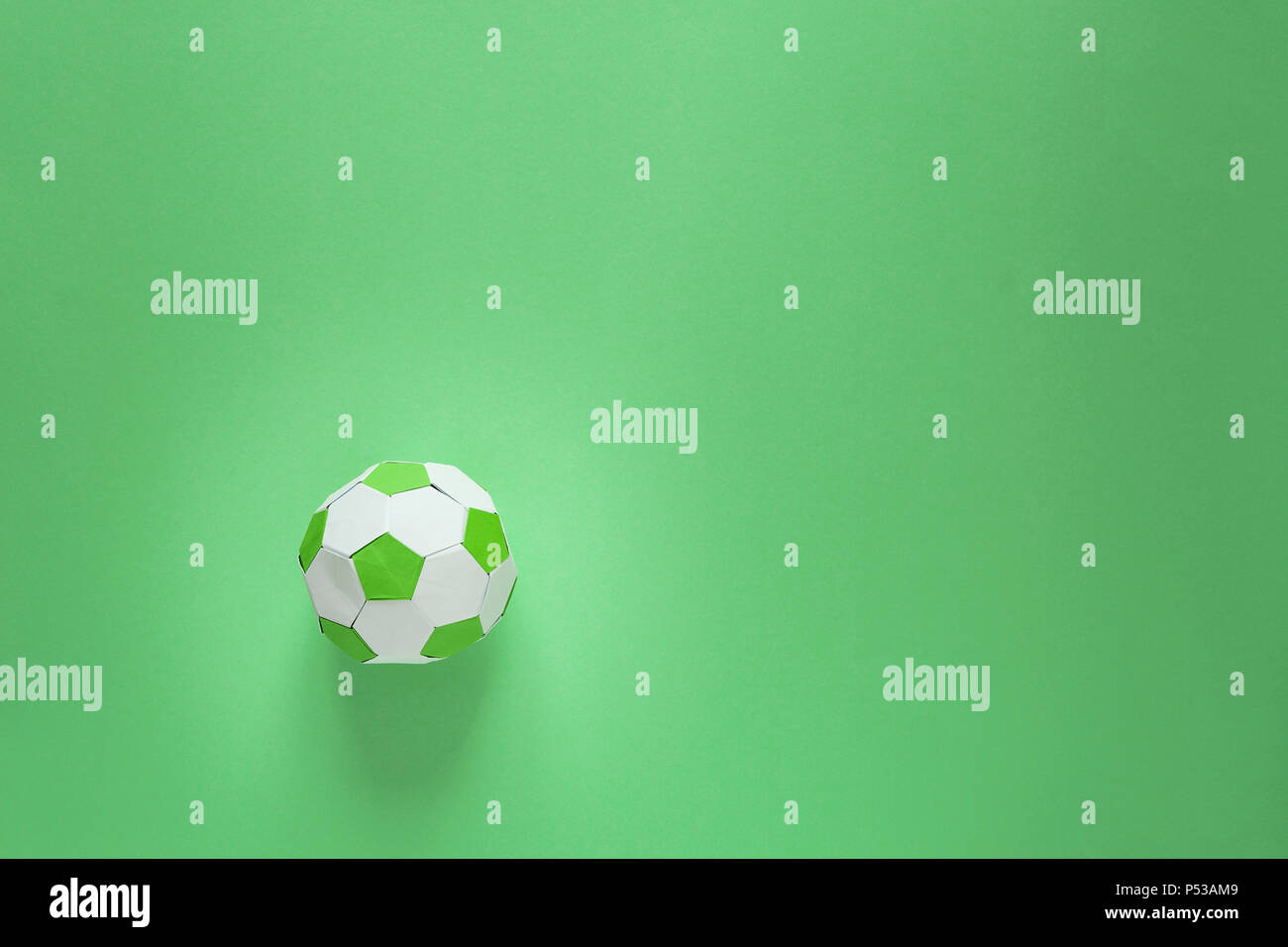 Balón de fútbol de papel en el campo de fútbol o fondo verde. El origami e5b42f4f53a20