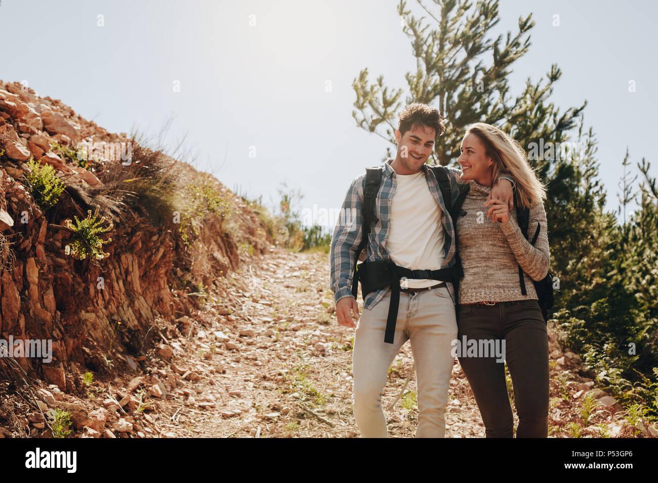 Amorosa pareja joven caminando por el sendero de montaña y sonriente. Pareja caucásica divertirse en día de caminata. Imagen De Stock