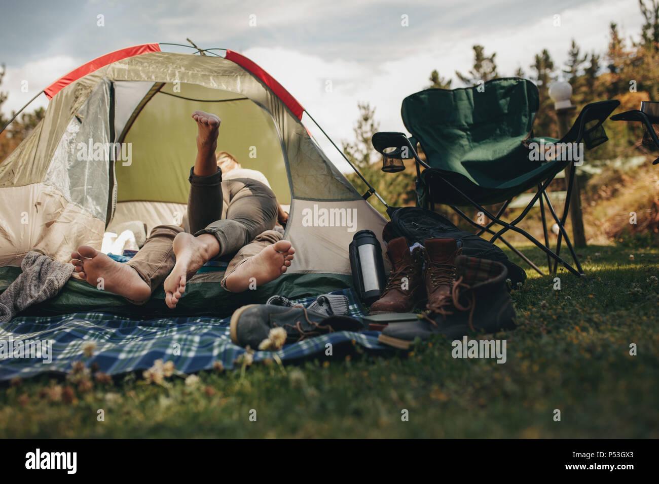Romántica pareja joven acostado en el interior de una tienda de campaña en el camping. El hombre y la mujer en el amor en una tienda de campaña. Imagen De Stock