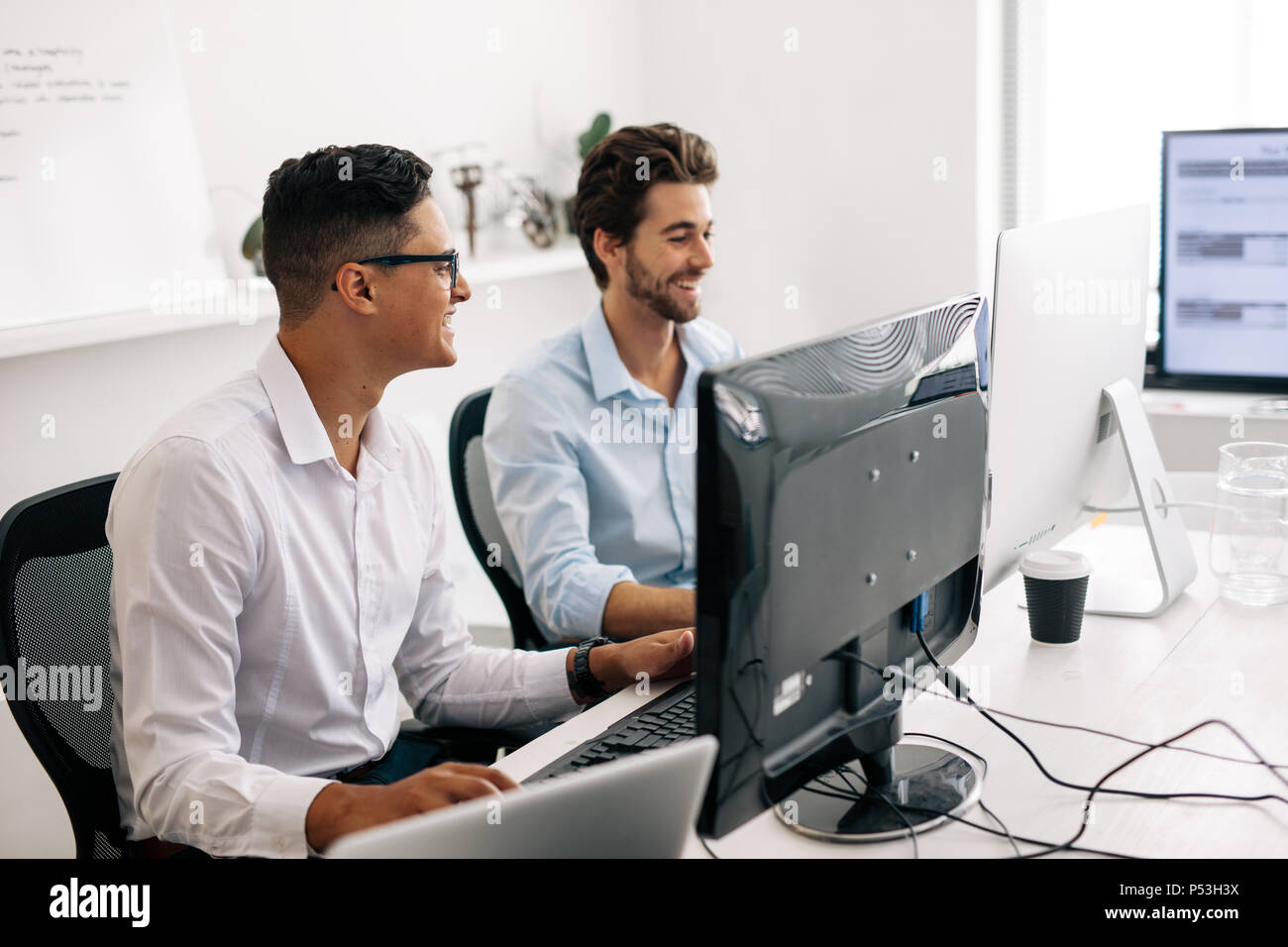 Los desarrolladores de software sentado en la oficina trabajando en equipos. Los desarrolladores de aplicaciones sonriente hablando mientras trabajan en los equipos de oficina. Imagen De Stock