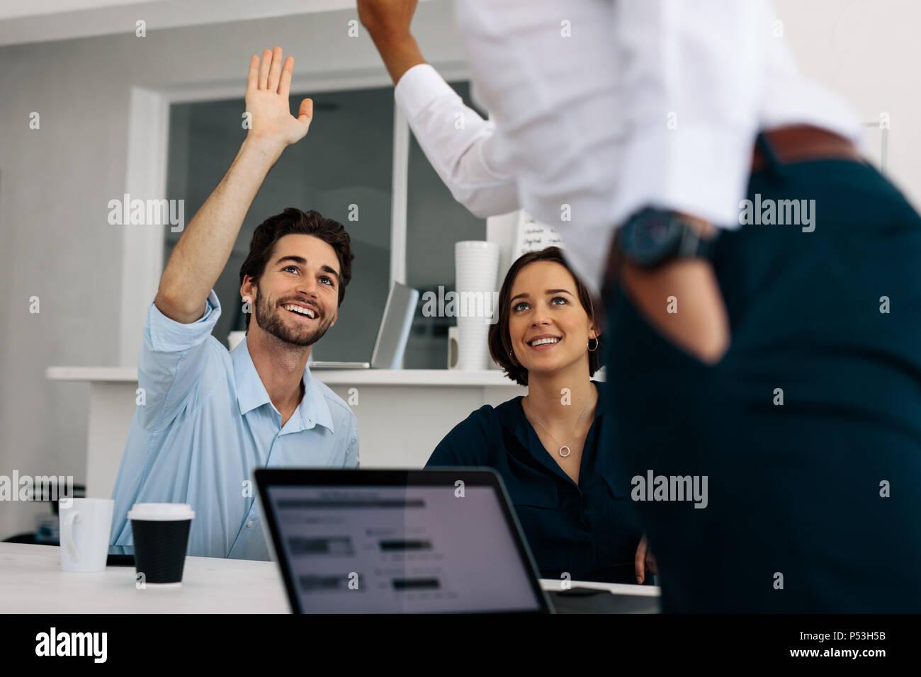 Los compañeros de negocio dando una alta cinco sentados en la mesa de conferencias. Los desarrolladores de aplicaciones discutiendo trabaje sentado en la sala de reunión. Imagen De Stock
