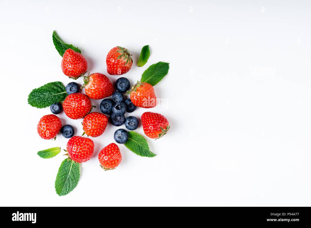 Bayas frescas sobre fondo blanco, vista superior. Las fresas, moras azules y hojas de menta, laicos plana Foto de stock
