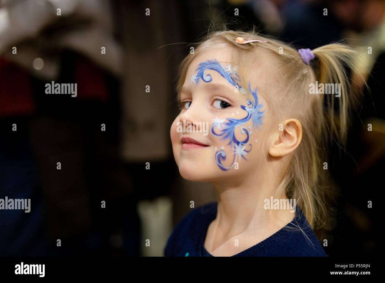 Poco lindo rubia chica con pintura de cara. Abstracto azul patrón de copo de nieve por acuarela sobre niños cara. Adorable niño con coloridos dibujos. Los niños Imagen De Stock