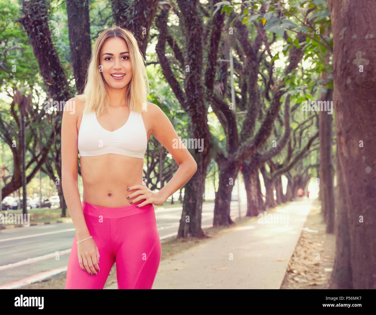 72984510c Mujer deportiva con la mano en la cintura. Ruta boscosa en la espalda.  Seguro