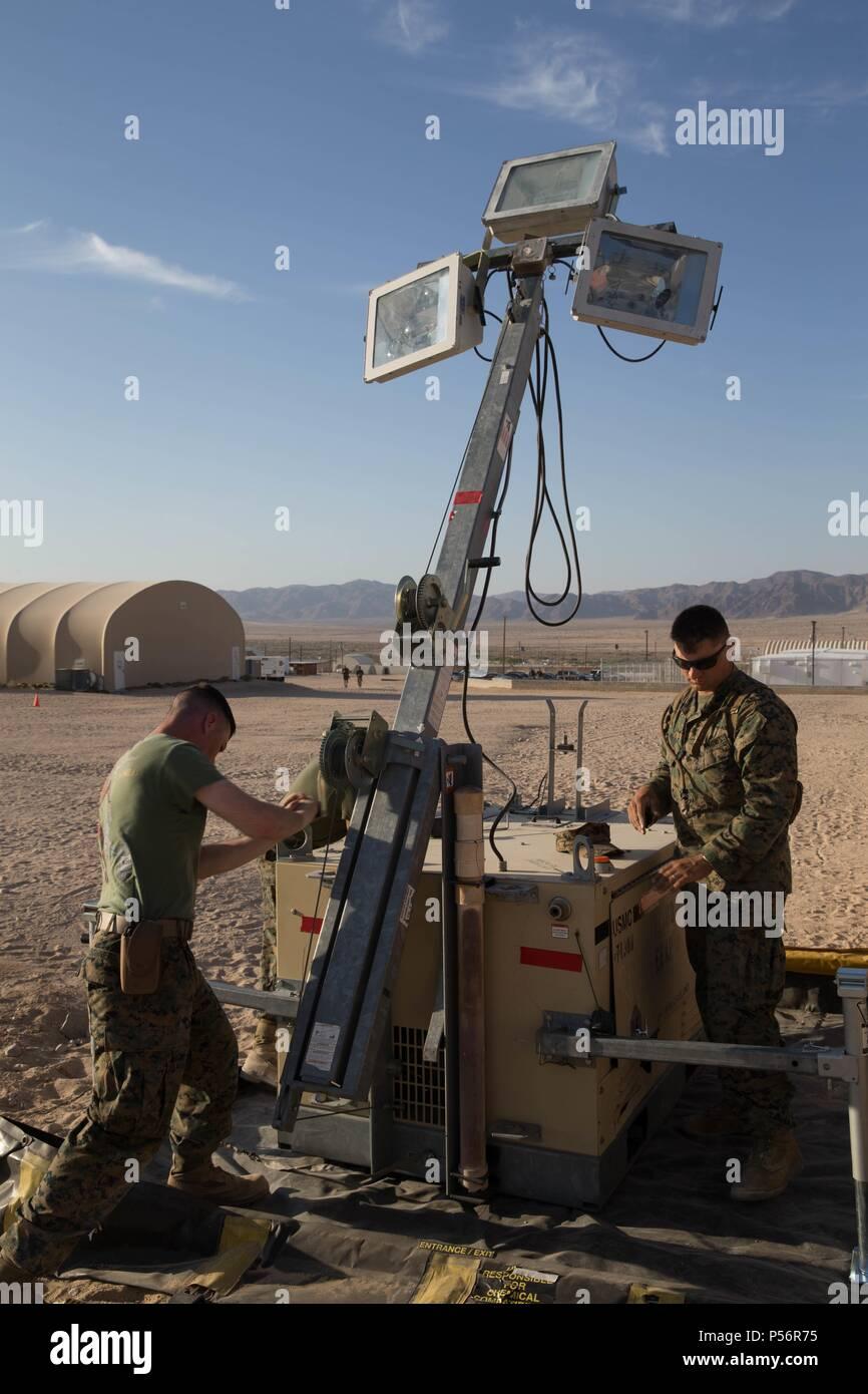 El Sargento. Lucas blanco, un ingeniero técnico de sistemas eléctricos de equipos con la empresa de mantenimiento, luchar contra el batallón de logística 451 del Regimiento de logística de combate, 45, 4º Grupo de Logística Marítima, y Lance Cpl. Eli Sommers, un técnico de refrigeración y aire acondicionado con utilidades, CLR-45, 4º MLG, levantar un foco durante el ejercicio de capacitación integrado 4-18 en la Infantería de Marina Centro de combate aire-tierra Twentynine Palms, California, 12 de junio de 2018, 12 de junio de 2018. Infantes de Marina con el elemento de apoyo de ejercicio de ITX 4-18 proporcionó el servicio de alimentos, procesamiento de llegada y salida, combustible a granel, en el campamento de ingeniería Foto de stock