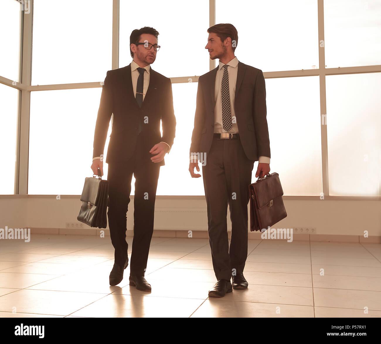 Imagen de fondo. Dos hombres de negocios de pie en el vestíbulo de la oficina Foto de stock