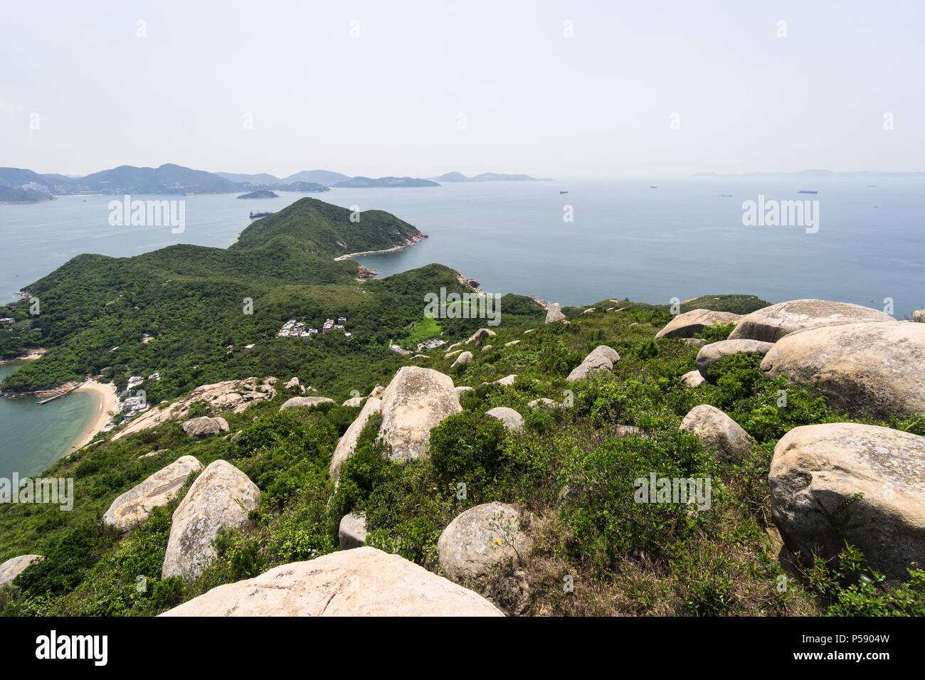 Impresionantes vistas de la escarpada costa de la isla de Lamma con la isla de Hong Kong en el fondo de la RAE de Hong Kong, China Imagen De Stock