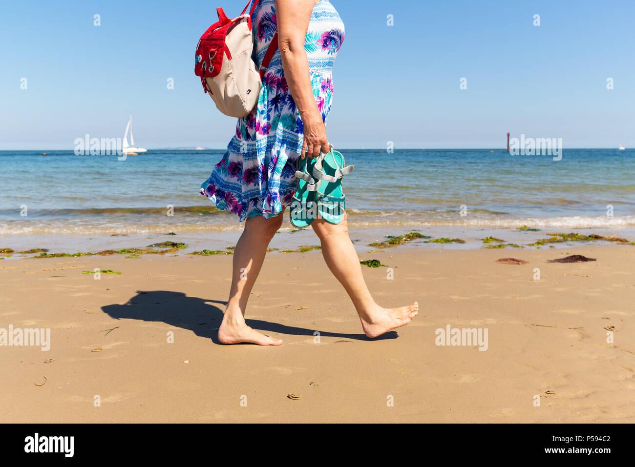 f17a5a636 Mujer caminando a lo largo de una playa de arena que llevaba un vestido de  verano con los pies descalzos, una mochila y llevar un par de sandalias.