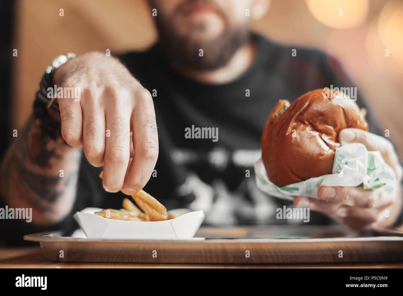 Joven barbudo hombre comiendo una hamburguesa y patatas fritas. Imagen De Stock