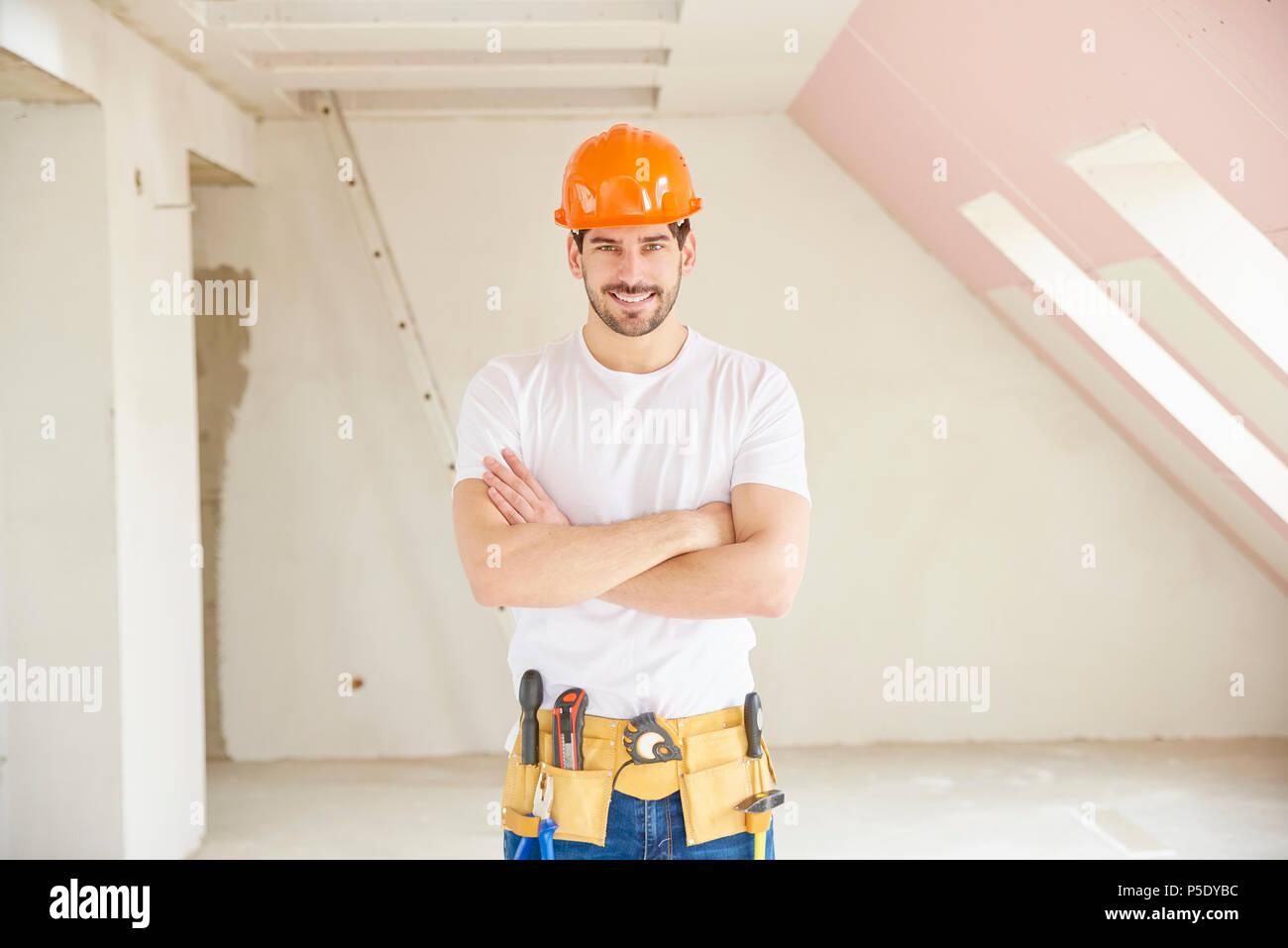 Apuesto joven manitas llevar sombrero duro y cinturón de herramientas  mientras está parado en el sitio 6095a4c86f6c