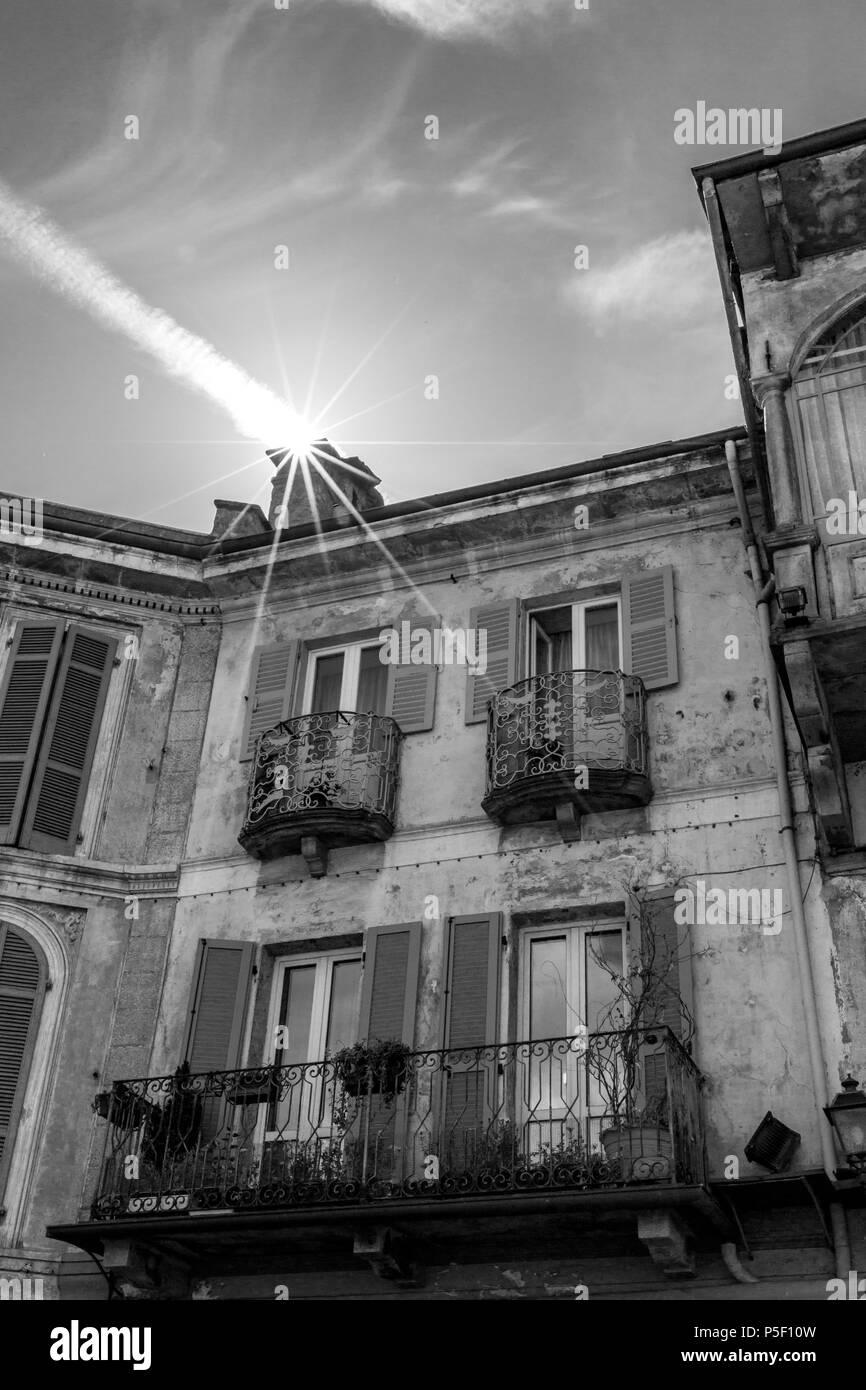 Ilusión Visual de Sol entra en una casa a través de la chimenea en el norte de Italia. Avión de estelas de vapor. Street View, imagen en blanco y negro. Imagen De Stock