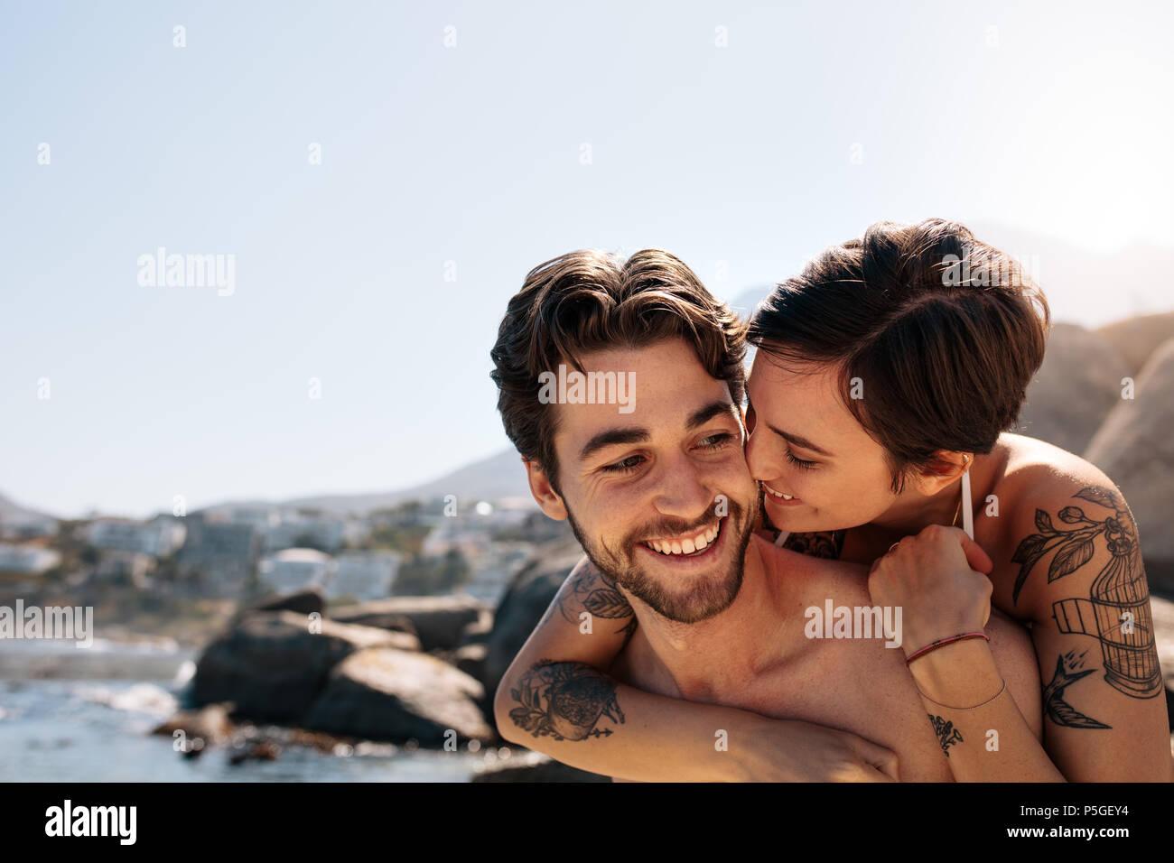 Mujer divirtiéndose caballo piggy back sobre el hombre en la playa. Pareja de turistas en un ambiente romántico y felices disfrutando de unas vacaciones. Imagen De Stock