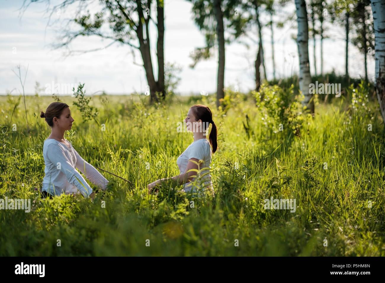 Retrato de dos jóvenes mujeres disfrutando de pranayama o ejercicios de respiración, relajarse, sentirse vivo y soñando Imagen De Stock