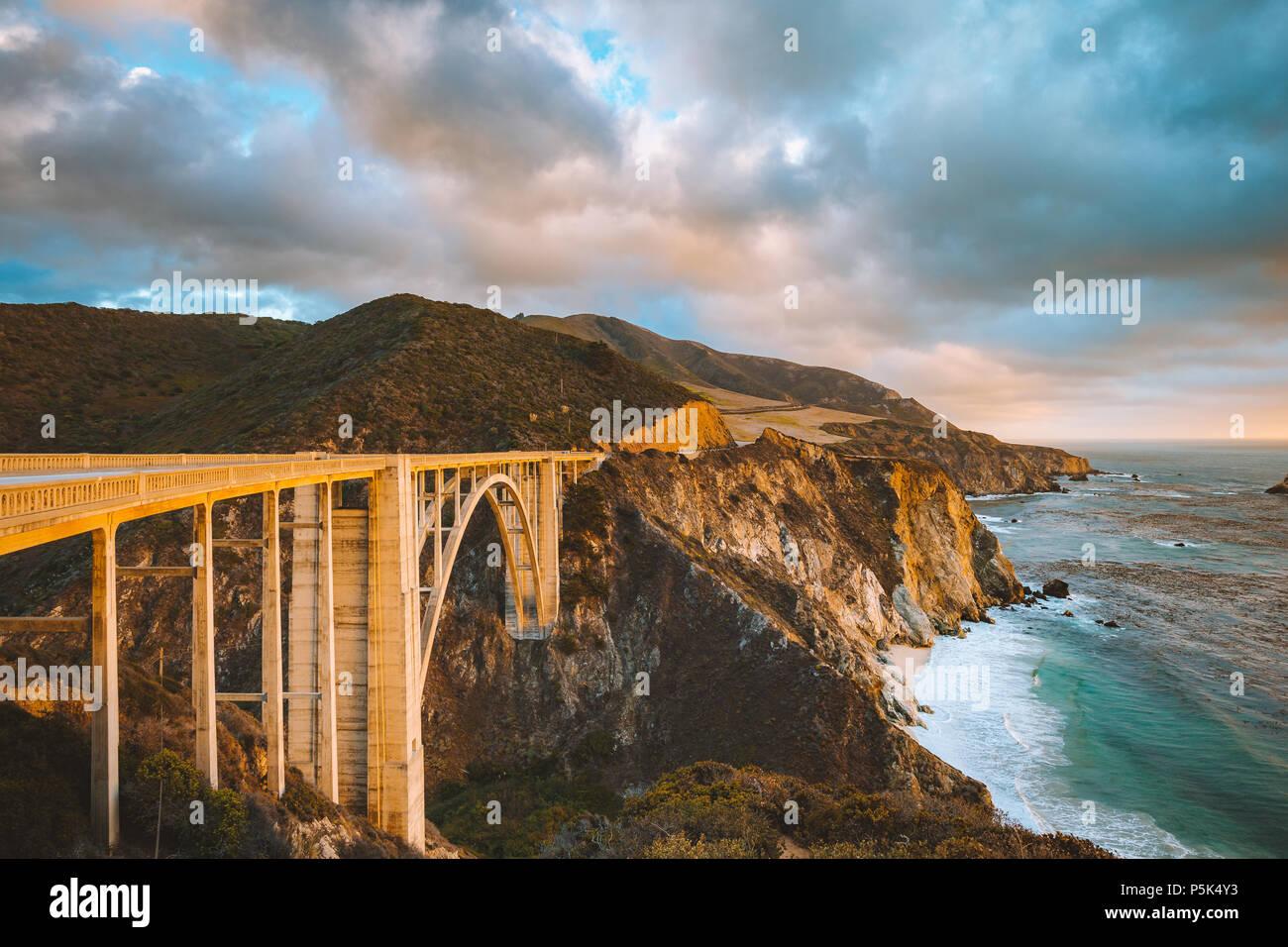 Pintoresca vista panorámica del casco histórico de Bixby Creek mundialmente famoso puente a lo largo de la autopista 1 en la hermosa luz del atardecer dorado al atardecer con dramáticas cloudscape Foto de stock