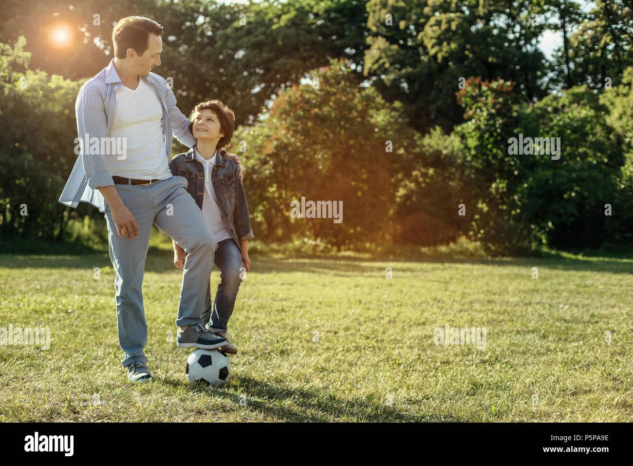 Papá y el muchacho descansar mientras jugaba al fútbol Imagen De Stock