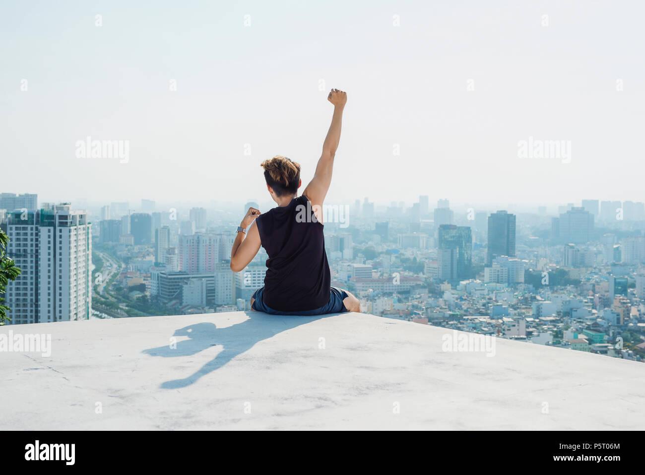 Hombre sentado en el techo negro y mostrar la mano con fondo de cielo azul y sol,luchando contra el hombre en el techo Foto de stock