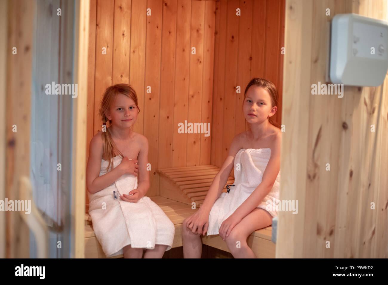 Dos niñas han envuelto en toallas y están sentados en una