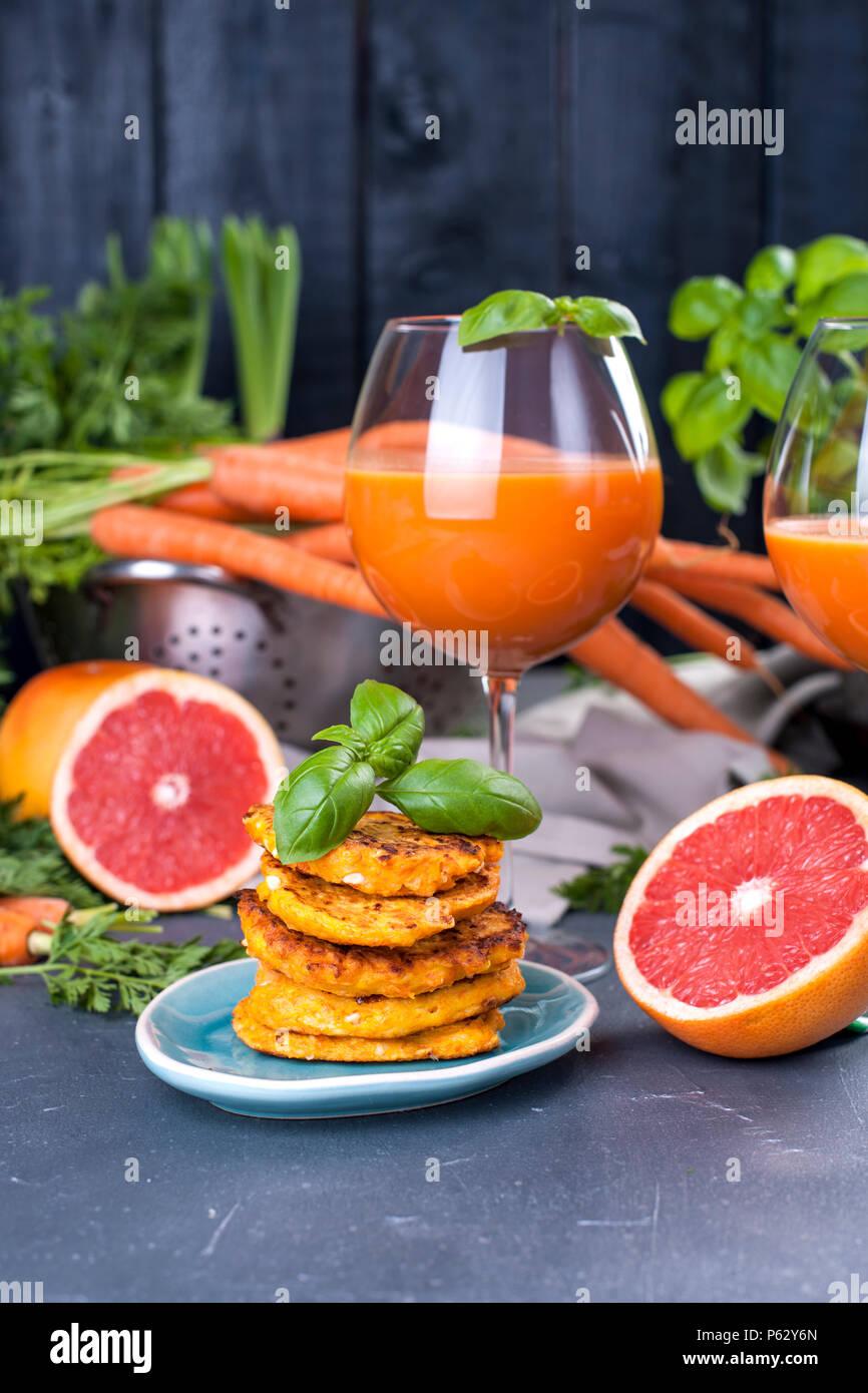 Jugo de zanahorias frescas y toronja en un vaso y fragantes tortitas de desayuno. Vitamina bebida para una dieta saludable. Las vitaminas en los alimentos. Espacio de copia Imagen De Stock
