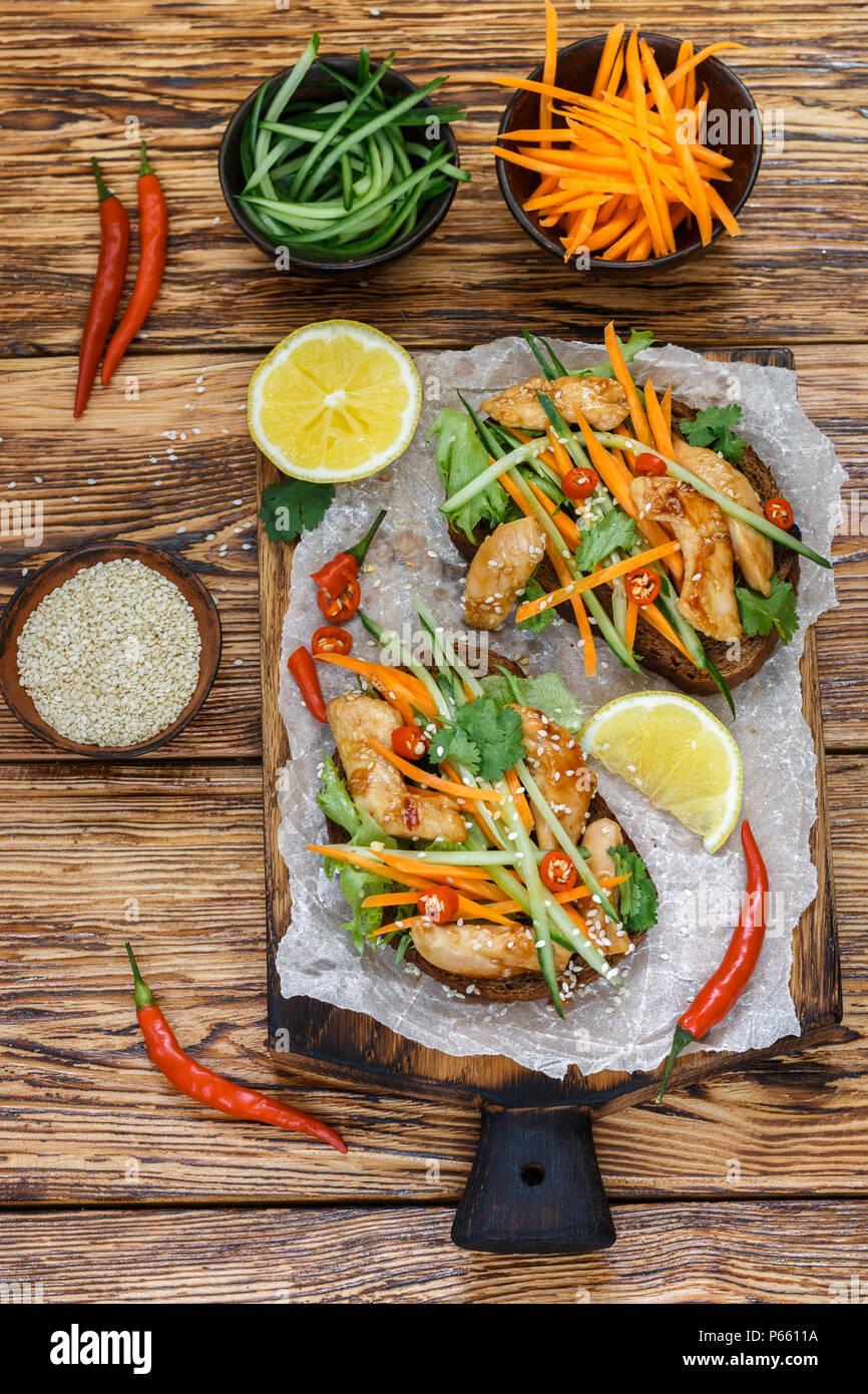 Asian sándwich con pollo frito y verduras frescas de la zanahoria, el pepino, el pimiento, el cilantro y el sésamo. El enfoque selectivo. Vista superior Imagen De Stock