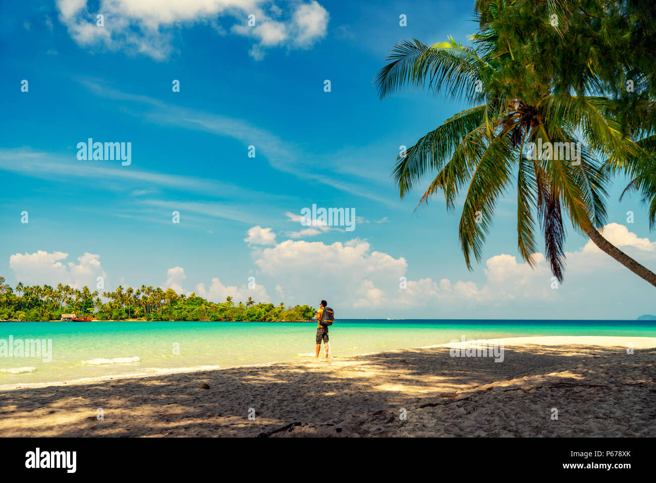 51d987519c087 Joven Hombre viajero con mochila quedándose solos en la playa y mirando al  océano