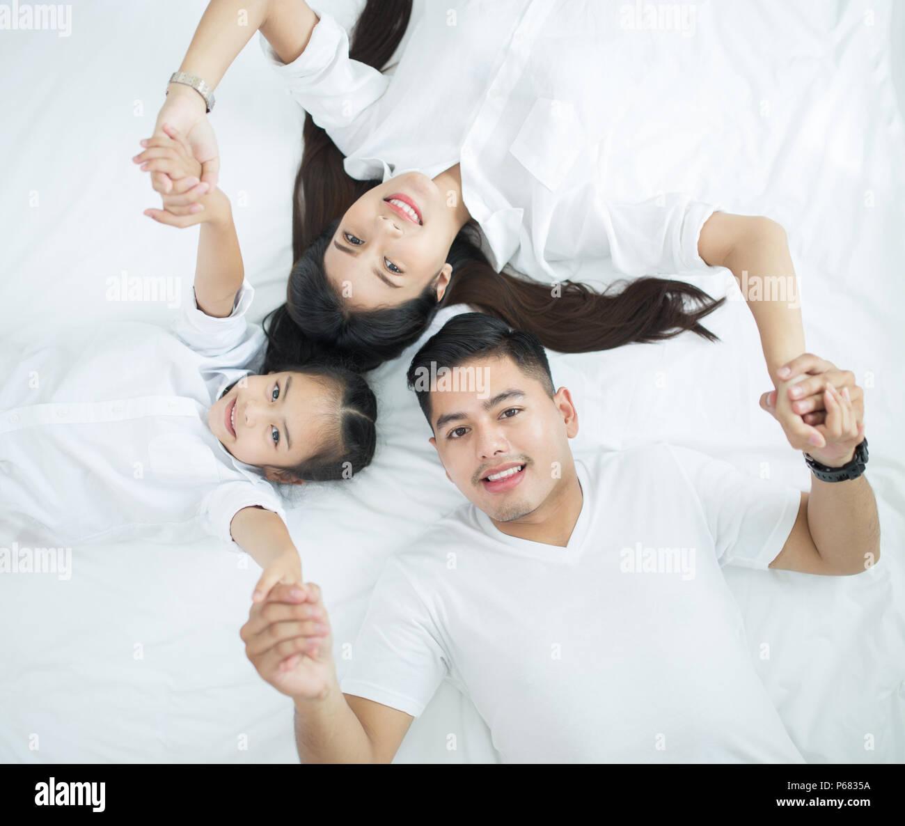 Las familias jóvenes con niños en la cama Imagen De Stock