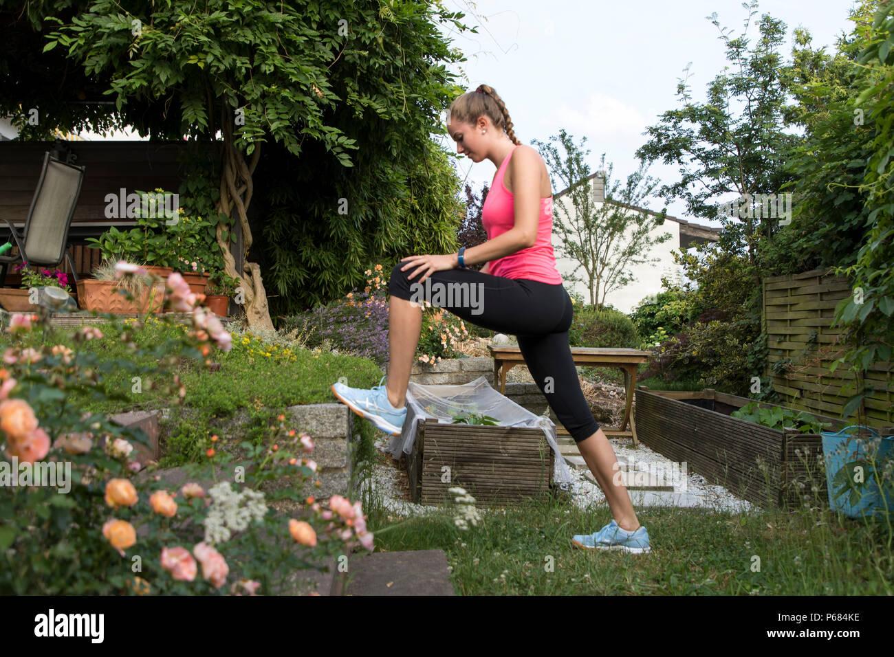 Mujer joven hacer ejercicios de estiramiento, antes de ejecutar una prueba de endurance, trotar, Foto de stock