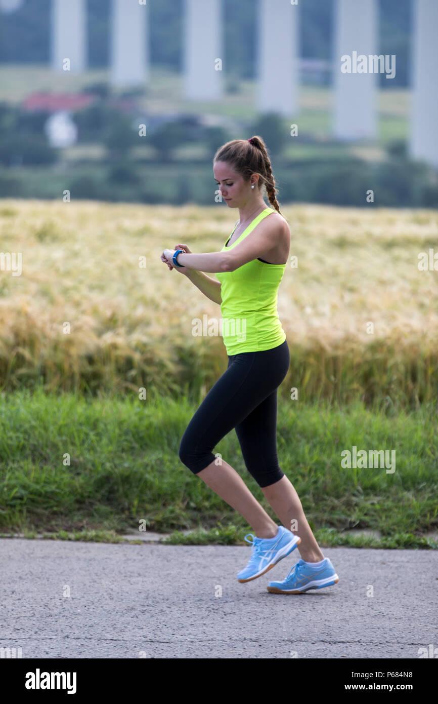 Mujer joven trotar, correr, controlar sus signos vitales en un reloj de fitness, fitness tracker, la frecuencia cardíaca, el número de pasos, distancia, tiempo y calorías quema Imagen De Stock