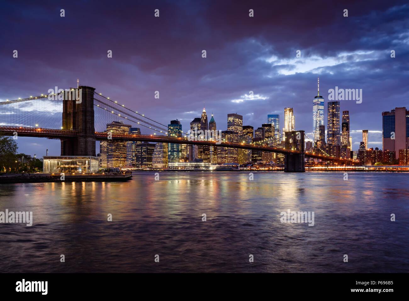 Puente de Brooklyn y Manhattan iluminada rascacielos al anochecer con el East River. Manhattan, Ciudad de Nueva York, EE.UU. Imagen De Stock