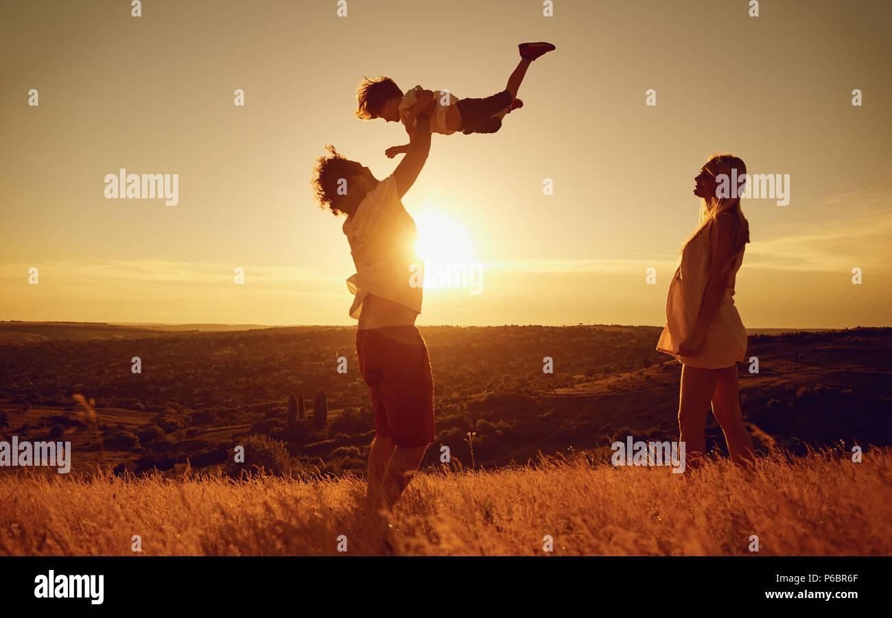 Familia Feliz divertirse jugando al atardecer en la naturaleza. Imagen De Stock